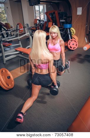 Athletic girls are doing knee-bends with dumbbells in the gym