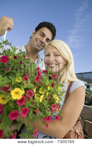 Couple Standing In Plant Nursery Holding Hanging Plant, Portrait, Low Angle View