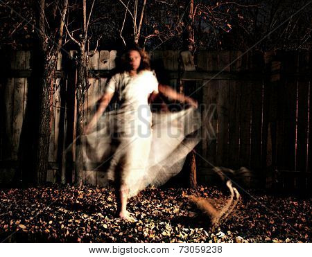 a woman in a very foggy forest at night with a yellow cat and motion blur caused by slow shutter speed with a grainy filter applied