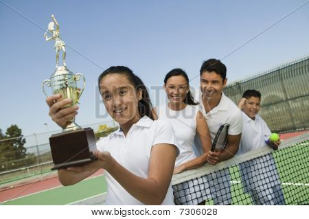 Tennis Family on court by net daughter holding trophy portrait