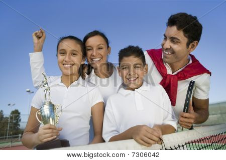 Tennis Family at net on tennis court daughter holding trophy portrait