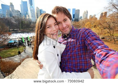 Dating young couple happy in love taking self-portrait selfie photo in Central Park, New York City in late fall early winter with skating rink in background. Tourists having fun date, Manhattan, USA.