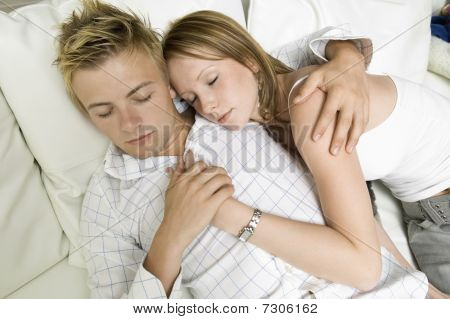 Young couple lying on sofa together close up high angle view