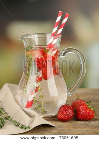 Tasty cool beverage with strawberries and thyme, on light background