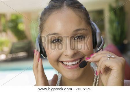 Retrato de joven en piscina con auriculares cerca
