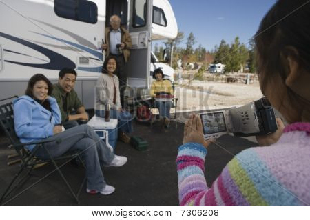 Young Girl videotaping family outside of RV