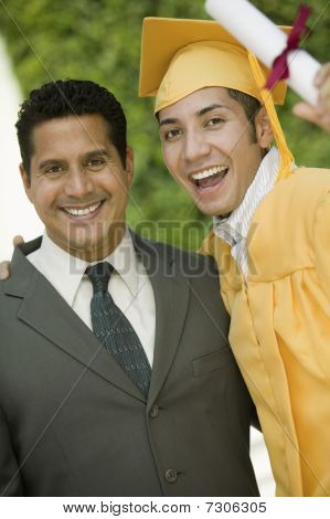 Graduate hoisting diploma with arm around father outside portrait
