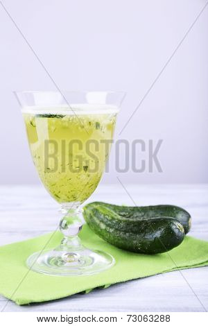 Cucumber cocktail on napkin on wooden table on light background