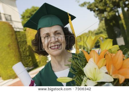 Senior Graduate holding diploma and flowers outside portrait