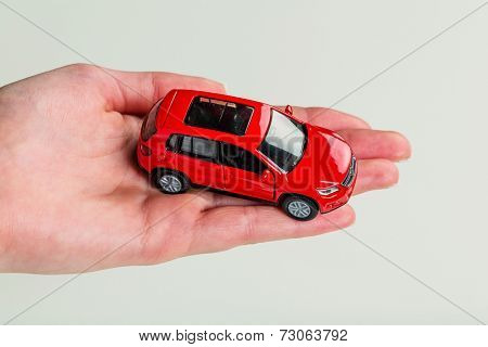a hand holding the model of a car. symbol photo for car purchase