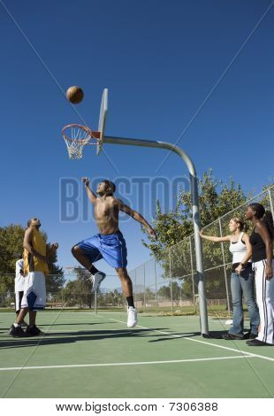 Group of young people playing basketball one player jumping for ball