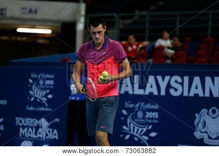 SEPTEMBER 23, 2014 - KUALA LUMPUR, MALAYSIA: Bernard Tomic of Australia prepares to make a serve in his first round match at the Malaysian Open Tennis 2014 event. This is an ATP sanctioned tournament.