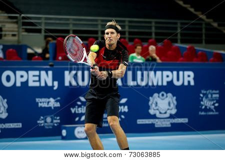 SEPTEMBER 23, 2014 - KUALA LUMPUR, MALAYSIA: Jarkko Nieminen of Finland makes a backhand return in his first round match at the Malaysian Open Tennis 2014 event. This is an ATP sanctioned tournament.