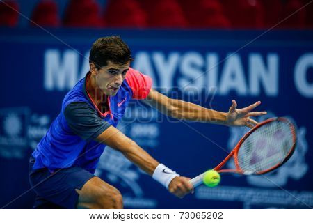 SEPTEMBER 25, 2014 - KUALA LUMPUR, MALAYSIA: Pierre-Hugues Herbert of France makes a backhand return in his match at the Malaysian Open Tennis 2014. This is an ATP sanctioned tournament.
