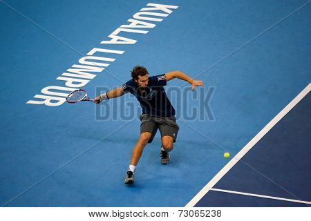 SEPTEMBER 25, 2014 - KUALA LUMPUR, MALAYSIA: Ernests Gulbis of Latvia attempts a forehand return in his match at the Malaysian Open Tennis 2014. This is an ATP sanctioned tournament.
