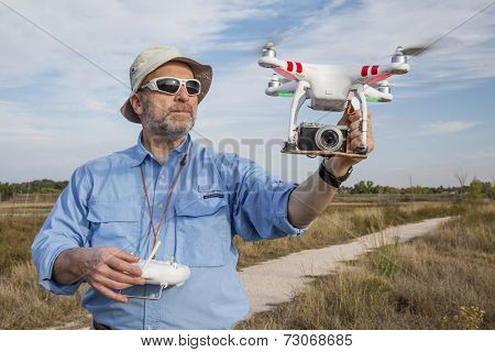 FORT COLLINS, CO, SEPTEMBER 28, 2014:  A senior male pilot and photographer is launching the DJI Phantom 2 quadcopter drone with Panosonic Lumix GM1 camera on board