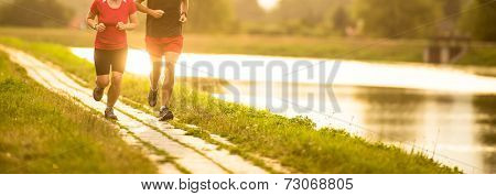 Couple running outdoors, at sunset, by a river, staying active and fit (color toned image)