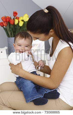 Happy little boy sitting on mother's lap, smiling.