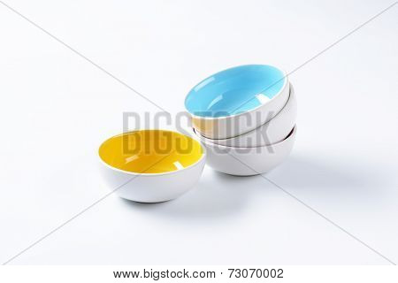 four ceramic bowls with blue and yellow on top