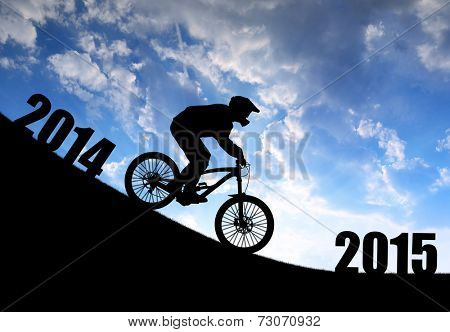 Silhouette of the cyclist on downhill bike at sunset .Forward to the New Year 2015