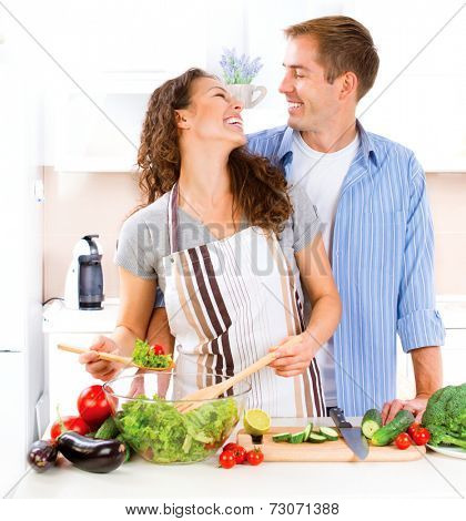 Happy Couple Cooking Together - Man and Woman in their Kitchen at home Preparing Vegetable Salad.Diet.Dieting. Healthy Food. Vegan food concept