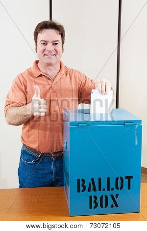 White male mid adult voter dropping his ballot in the box and giving a thumbs up.