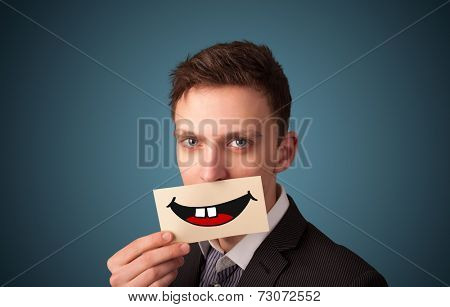 Happy man holding card with funny smiley on gradient background