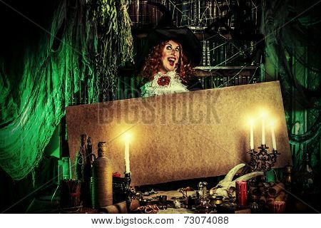 Attractive witch in the wizarding lair. Fairytales. Halloween. Copy space.