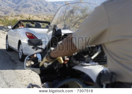 Police officer on motorbike stopping car on desert road side