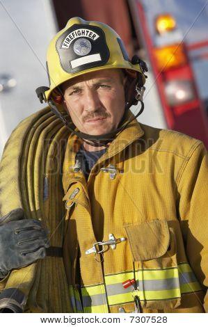 Fire fighter holding hose on shoulder