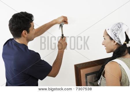 Couple hanging picture on interior wall back view