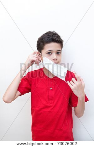 A sick young boy putting on a face mask to stop spread of germs.
