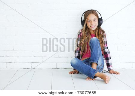 8-9 years old stylish teen girl with black headphones posing on white background