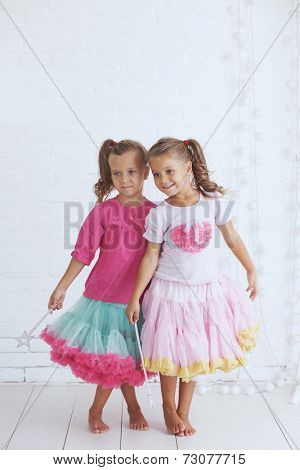Studio portrait of two cute little princess girls wearing holiday candy tutu skirt holding magic wand