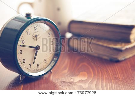 analog retro alarm clock on wooden table