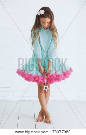 Studio portrait of cute little princess girl wearing holiday candy tutu skirt holding magic wand