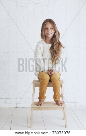 Cute little girl 8-9 years old wearing knit trendy winter clothes posing over white brick wall