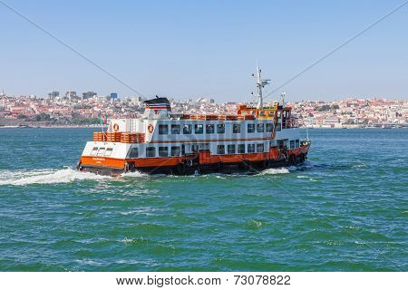 Lisbon, Portugal. August 31, 2014: A Lisbon ferry, known as a Cacilheiro departs from the south margin of the Tagus river in Cacilhas to connect the city of Almada to the capital seen in the horizon.