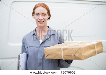 Delivery driver smiling at camera by her van holding parcel outside the warehouse