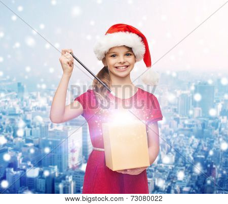 christmas, holidays, happiness and people concept - smiling girl in santa helper hat with gift box and magic wand over snowy city background