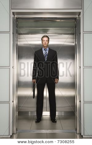 Businessman standing in open Elevator portrait front view