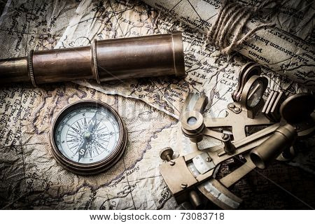 vintage still life with compass ,sextant ,spyglass ,and old map.map used for background is in Public domain. Map source: Library of Congress. Belgium Year: 1570 Author Abraham Ortelius 1527-1598
