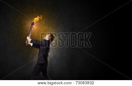 Young businessman holding burning torch in hand