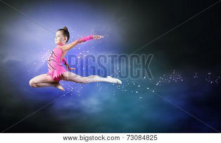 Little cute girl gymnast making high jump