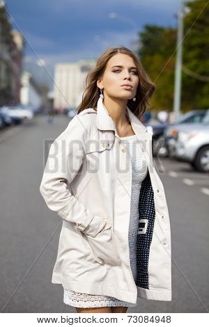 Portrait close up of young beautiful woman in white coat