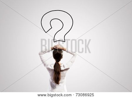Rear view of businesswoman looking thoughtfully at question mark above head