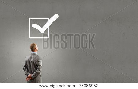 Rear view of businessman looking at tick above head