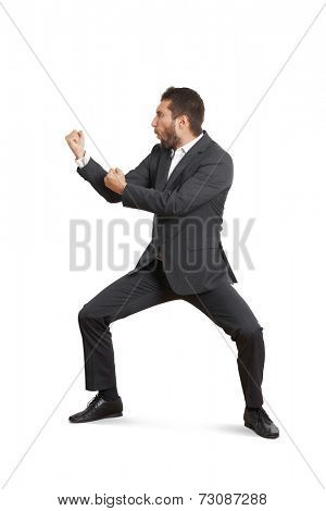 funny young businessman in formal wear beating his fist. isolated on white background