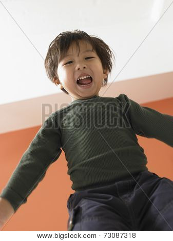 Young boy jumping on bed