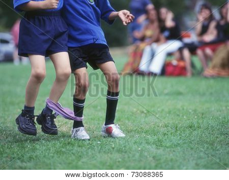 Low section of two boys in three-legged race